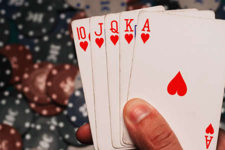 Royal flush in the hands of the player on the background of game chips
