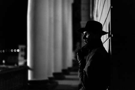 dark silhouette of a man in a raincoat with a hat and a scar on his face at night Banco de Imagens