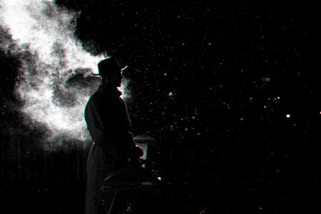 dramatic silhouette of a dangerous man in a hat at night in the rain in the city Banco de Imagens