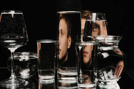 portrait of a man through the glass of the tank with water with the reflections and distortions