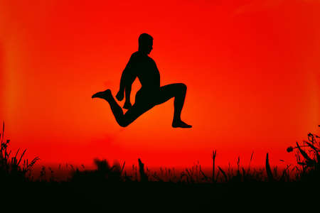 silhouette of a sporty man jumping high in nature Banco de Imagens