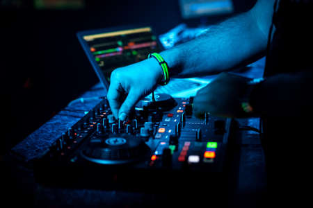 hand DJ mixing music on a professional controller Board Banco de Imagens