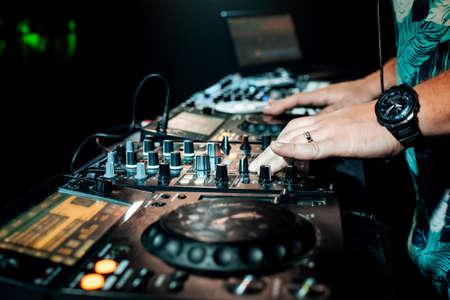 DJ hand mixes on a professional mixer controller at a concert Banco de Imagens
