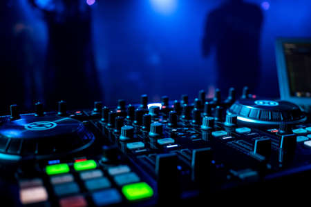 professional DJ music mixer in a nightclub with buttons
