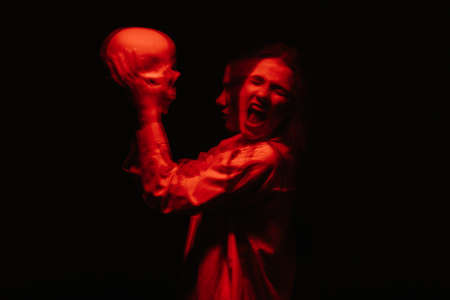 scary blurry portrait of a female witch with a skull in her hands Фото со стока