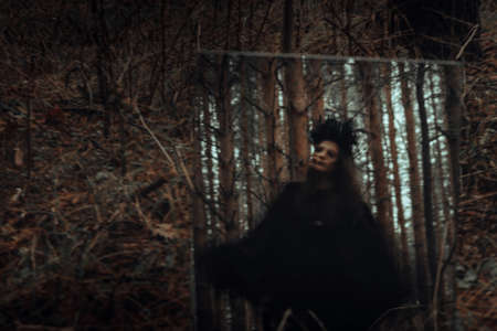 blurred mystical silhouette of an evil terrible witch in a mirror Фото со стока