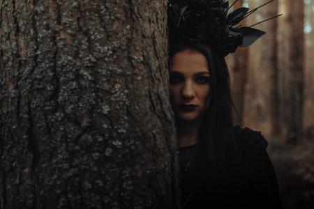 dark portrait of a frightening witch in black costume