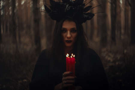 witch in a black costume holds candles in a dark forest