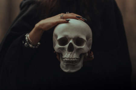 skull of a dead man in the hands of a witch witch