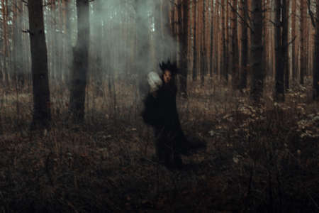 blurry silhouette of an evil black witch with a skull in her hands performing an occult satanic ritual