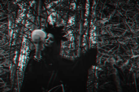 blurry mystical reflection of a black witch with a skull in her hands performing a satanic ritual