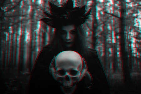 portrait of a terrible witch with a skull in the hands of a dead man performs an occult mystical ritual