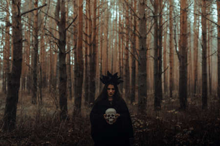 black terrible witch with a skull in the hands of a dead man