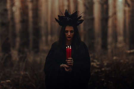 black terrible witch holds candles in her hands Фото со стока