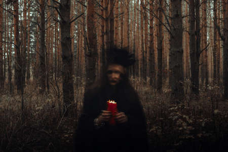 witch in a black costume with candles in her hands performs an occult ritual and mystical spells in a dark forest Фото со стока