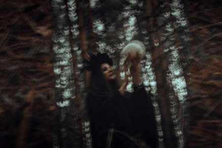 blurred reflection in the mirror of an evil scary witch with the skull of a dead man conjuring mystical occult rituals Фото со стока