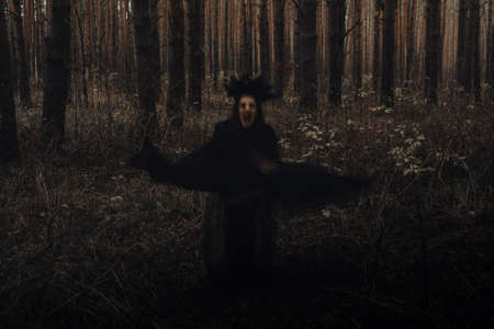 blurry frightening black silhouette of an evil witch Фото со стока