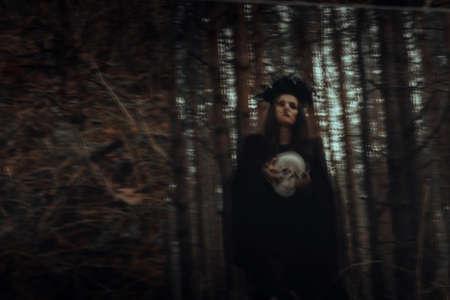 blurred mystical silhouette of an evil scary witch with a dead mans skull in a mirror Фото со стока