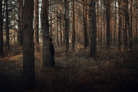 dark portrait of a terrible witch in a black suit in the forest