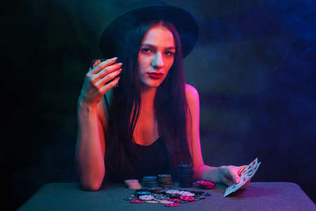 girl plays poker at a table with cards and chips in a casino