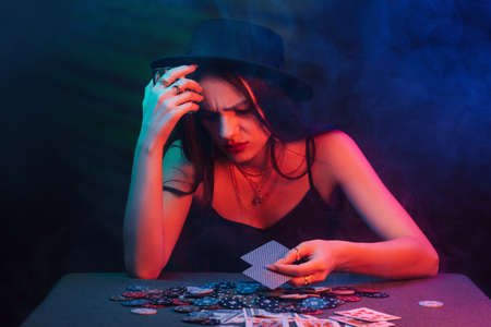 girl lost in the casino at the table with chips and cards