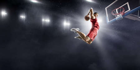 Baketball player making a slam dunk on a professional basketball arena. He wears unbranded clothing.