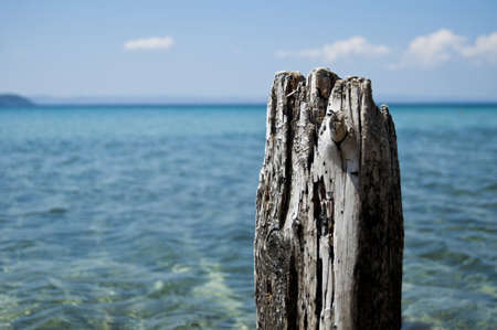 Old wood post with sea in the background on a sunny day Stock Photo