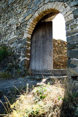 Old medieval fortress door open with sun shining through photo