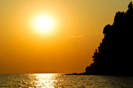 Sunset at the sea horizon with island silhouette