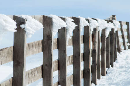 Old wooden fence covered in snow in the mountain Stock Photo
