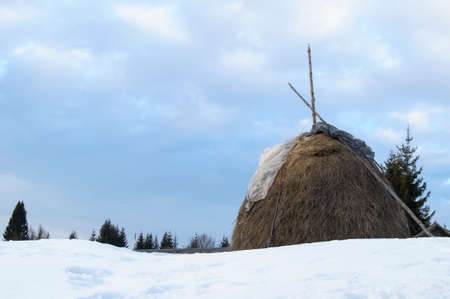Haystack in winter in the mountain Stock Photo