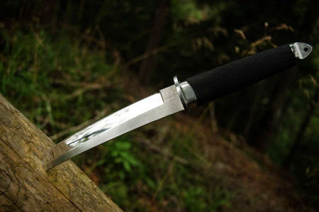 Japanese style tanto knife stuck in wood Stock Photo