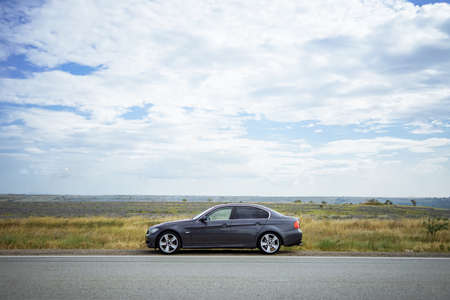 Car on the road on the background of a field