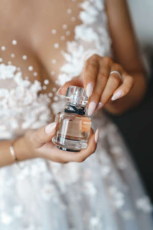 Perfume bottle in hand close up.