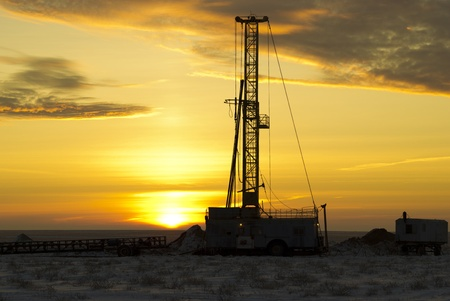 the drilling rig against a sun dawn photo