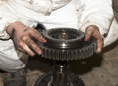 dirty hands: the worker dirty hands holds a big gear in auto service