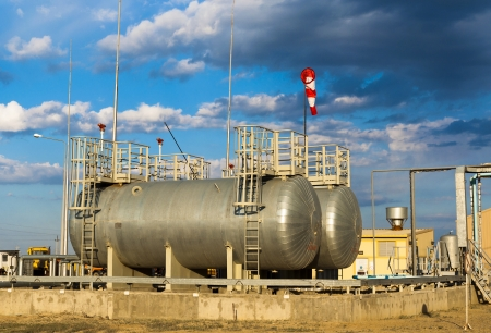 capacities: capacities for fuel on a production site against the cloudy sky Stock Photo
