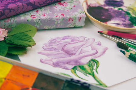 watercolor sketch of a purple rose with brushes and paints 스톡 콘텐츠