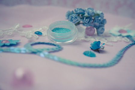 sequins: rhinestones, sequins and paper flowers on a pink background