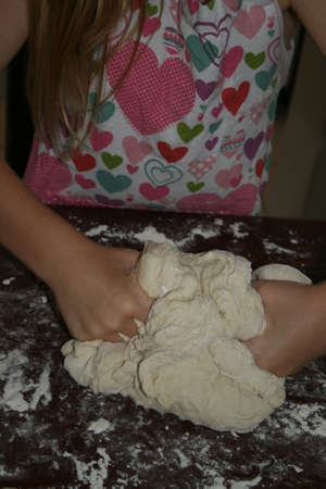 Young girl kneading bread dough Stok Fotoğraf