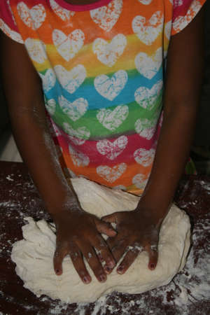 kneading: Young girl kneading bread dough Stock Photo