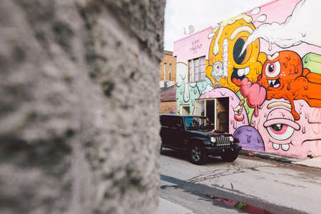 Lost car beside graffiti wall Editorial