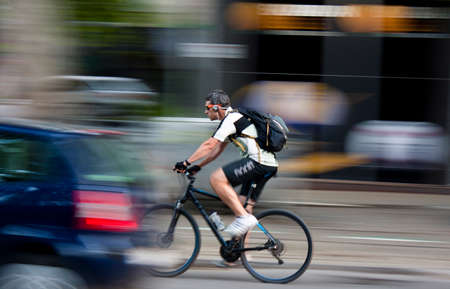 panning shot: Cyclist on the busy city street in summertime, motion blur. Belgrade, Serbia - 29. June, 2016.
