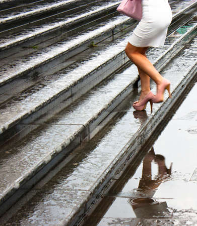 Woman in mini skirt and high heels, holding a purse, climbs up the wet stairs of the Temple of Saint Sava, and makes reflection in the puddle. Shot from the waist down, just after the rain. Stock Photo