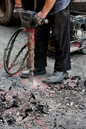 decibels: Worker jackhammering street. Shot from the waist down.