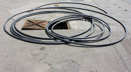Long hose around open manhole and a pair of gloves 免版税图像