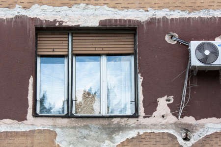 air hole: Belgrade, Serbia -  Jun 4, 2016: Detail of a neglected building facade in the center of Belgrade, with a window and an air condition unit.