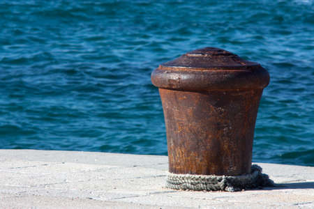 Big old rusty bollard on a stone pier, with a rope around it, and wavy blue sea in the background