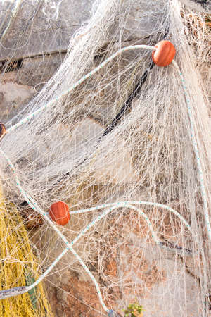 floaters: Detail of an abandoned fishing net on a stone pier