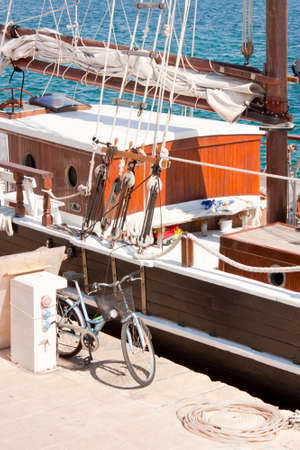 Electrical and water supply pedestal,  bike and a rope on the dock, next to the moored wooden sailboat. Editorial
